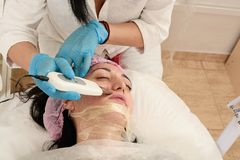 Young woman in beauty salon doing ultrasound peeling and facial cleansing procedure. Cosmetic multifunctional device. Ultrasound procedure. Medical equipment royalty free stock photography