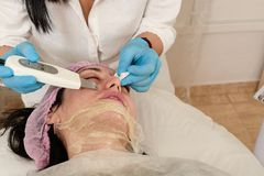 Young woman in beauty salon doing ultrasound peeling and facial cleansing procedure. Cosmetic multifunctional device. Ultrasound procedure. Medical equipment royalty free stock photos