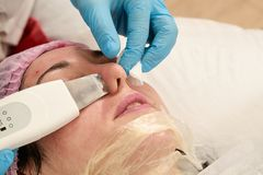 Young woman in beauty salon doing ultrasound peeling and facial cleansing procedure. Cosmetic multifunctional device. Ultrasound procedure. Medical equipment stock photography