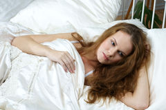 Young woman in bed Stock Images