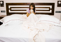 Young woman in bed. Enjoying a coffee in a huge bed Stock Photography