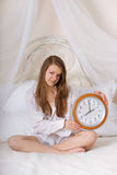 Young woman in bed and alarm clock Royalty Free Stock Photo