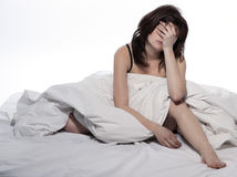 Young woman in bed awakening hangover. One young woman in bed awakening tired insomnia hangover  in a white sheet bed on white background Royalty Free Stock Photo