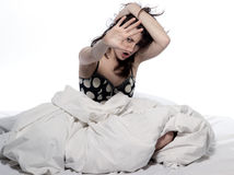 Young woman in bed awakening hangover. One young woman in bed awakening tired insomnia hangover  in a white sheet bed on white background Stock Photography