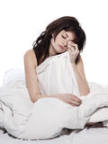 Young woman in bed awakening tired insomnia hangov. One young woman in bed awakening tired insomnia hangover  in a white sheet bed on white background Royalty Free Stock Photography