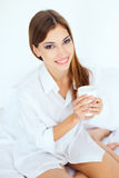 Young woman in bed with a cup of coffee Stock Photography