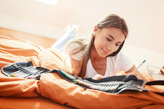 Young Woman On Bed, Drawing In Coloring Book Royalty Free Stock Photography