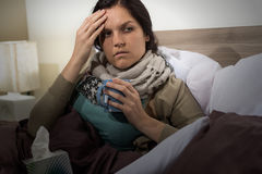 Young woman in bed having flu Stock Image