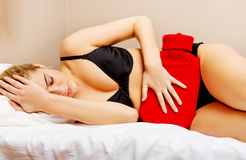 Young woman in bed, with hot water bag on her tummy Royalty Free Stock Images