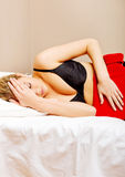 Young woman in bed, with hot water bag on her tummy Stock Photography