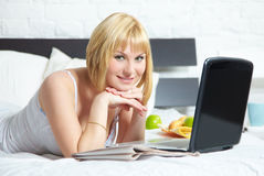 Young woman on bed with laptop Royalty Free Stock Images