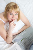 Young woman on bed with laptop Stock Image