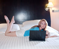 Young woman on a bed with a laptop. The young woman on a bed with a laptop Royalty Free Stock Photos
