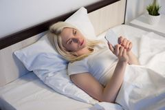 Young woman on bed late at night texting using mobile phone tired falling sleep. Image royalty free stock photography