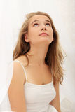 Young woman in bed looking up. Stock Photos