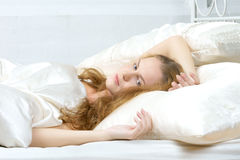Young woman in bed looking at you Stock Photography
