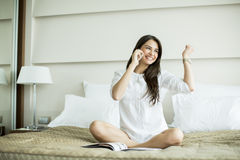 Young woman in the bed with mobile phone Stock Image