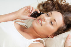 Young woman in bed with phone Royalty Free Stock Photo