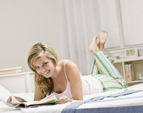 Young woman in bed reading magazine. Portrait of a Young woman in bed reading magazine Royalty Free Stock Image