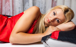 Young woman in bed in red underwear Stock Image
