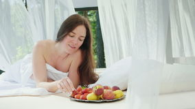 Young woman in bed with a strawberry in her hand. Lies by the pool on a lounger with curtains. Romance honeymoon. Breakfast in bed. HD video stock video footage