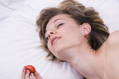 Young woman on bed with strawberry and sex toys Royalty Free Stock Photos