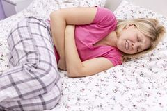Young woman in bed suffers from pain royalty free stock image