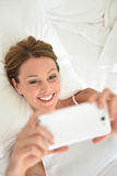 Young woman in bed taking selfie. Woman laying on bed and using smartphone Stock Photo