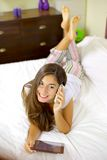 Young woman in bed talking on the phone with tablet Royalty Free Stock Images