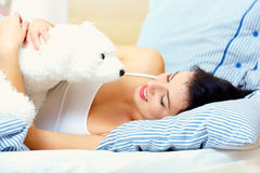 Young woman in bed with teddy bear Royalty Free Stock Photography