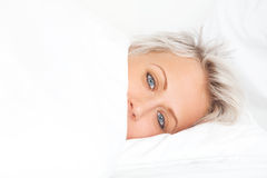 Young woman in bed under blanket Stock Photo