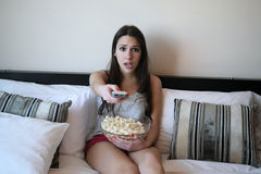 Young woman in bed watching a movie Royalty Free Stock Photo