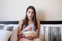 Young woman in bed watching a movie Stock Image