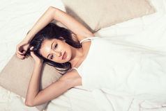 Young woman in bedroom on bed alone relaxing top view Stock Photos