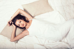 Young woman in bedroom on bed alone relaxing top view Royalty Free Stock Photos
