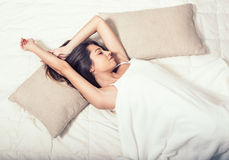Young woman in bedroom on bed alone relaxing top view Royalty Free Stock Photo