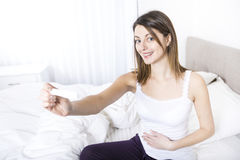 Young woman in bedroom at home wearing in white check pregnant test Stock Photo