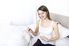 Young woman in bedroom at home wearing in white check pregnant test Royalty Free Stock Photos