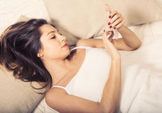 Young woman in bedroom with mobile phone in bedroom Royalty Free Stock Image