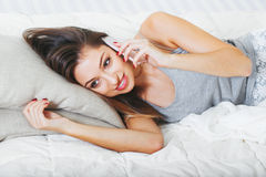 Young woman in bedroom with mobile phone portrait Royalty Free Stock Photography