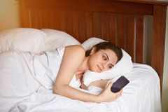 Young woman in bedroom with phone Stock Photo