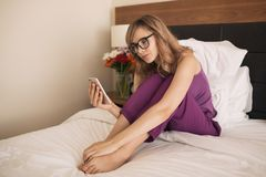 Young woman in bedroom. Using smartphone. royalty free stock photography