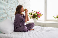 Young woman at the bedside in pajamas drinking tea on the backgr Stock Photography
