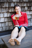 Young woman with beer. Young woman smiling with glass of beer and legs on table royalty free stock photo