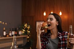 Young woman with beer eating tasty burger. In cafe stock image