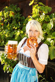 Young woman with beer glasses and bretzel. Woman with beer glasses and bretzel in traditional costume royalty free stock image