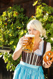 Young woman with beer glasses and bretzel. Woman with beer glasses and bretzel in traditional costume royalty free stock photo