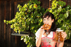 Young woman with beer glasses and bretzel. Woman with beer glasses and bretzel in traditional costume stock images