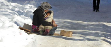 Young woman beggar on the icy  street is breastfeeding her baby Royalty Free Stock Photos