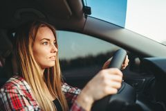 Young woman beginner driving a car, back view. Female person in vehicle, automobile driver concept royalty free stock image
